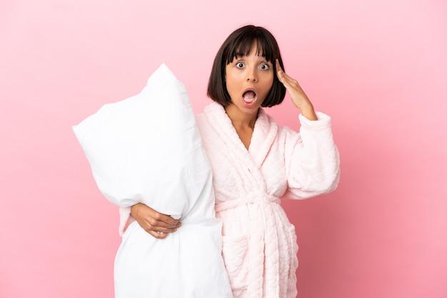 Kobieta w ciąży w piżamie na białym tle na różowym tle z wyrazem zaskoczenia