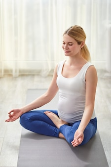 Kobieta w ciąży w pozie ardha padmasana pół lotosu na podłodze