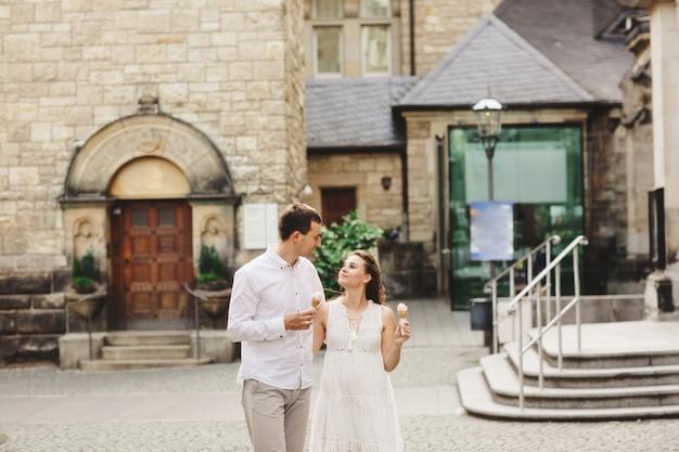 Kobieta w ciąży w sukience i jej mąż spacerują po mieście