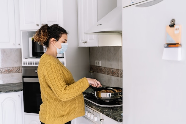 Kobieta w ciąży w żółtym swetrze do gotowania stojący w kuchni z maską na twarzy