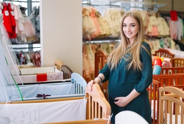Kobieta w ciąży wybiera łóżeczko dziecięce w sklepie.