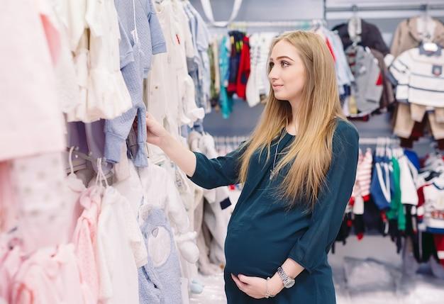 Kobieta w ciąży wybiera ubrania dla dzieci w sklepie.
