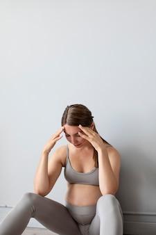 Kobieta w ciąży wygląda na zmęczoną po ćwiczeniach z kopią miejsca