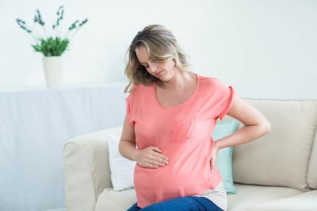 Kobieta w ciąży z bólem pleców w salonie