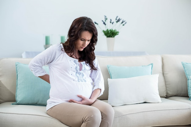 Kobieta w ciąży z bolesnym plecy w żywym pokoju
