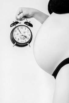 Kobieta w ciąży z budzikiem