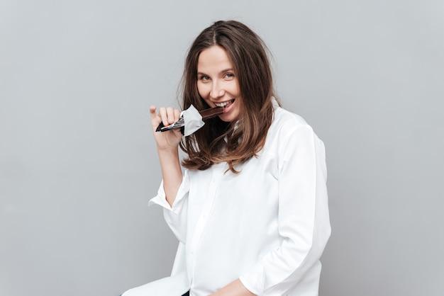 Kobieta w ciąży z czekoladą patrząca na aparat przebiegły na białym tle