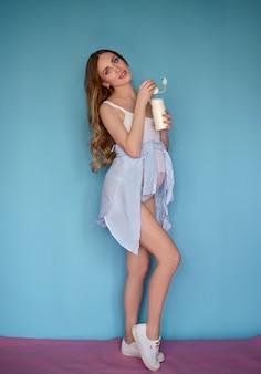 Kobieta w ciąży z długimi włosami iw stroju kąpielowym na wielokolorowym niebieskim tle pije koktajl mleczny portret studio mody