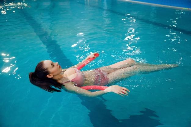 Kobieta w ciąży z dużym brzuchem pływająca w basenie pod dachem
