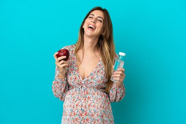 Kobieta w ciąży z jabłkiem i butelką wody