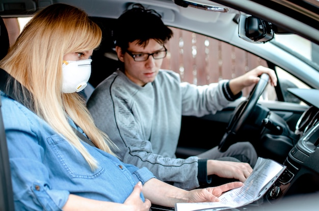 Kobieta w ciąży z maską ochronną, bóle porodowe w samochodzie jadącym do szpitala z mężem, rodząca w sytuacji pandemii koronawirusa, czytanie instrukcji w pojeździe