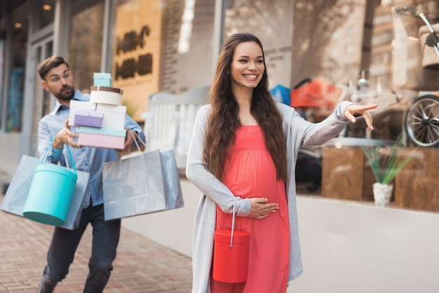 Kobieta w ciąży z mężczyzną idącym obok okna sklepu