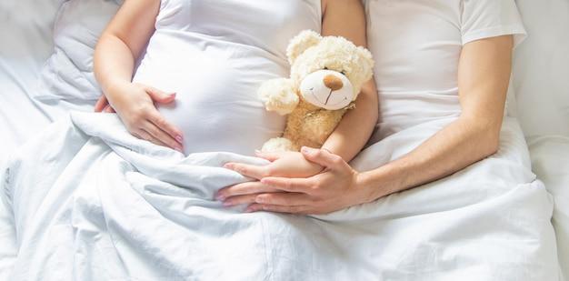 Kobieta w ciąży z mężczyzną trzymać zabawka przytulić brzuch. selektywne ustawianie ostrości.