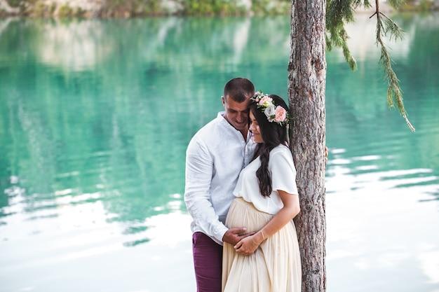 Kobieta w ciąży z mężem na jeziorze