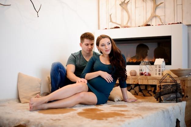 Kobieta w ciąży z mężem, siedząc przy kominku