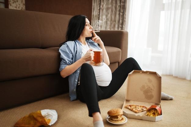Kobieta w ciąży z paleniem brzucha i pije piwo w domu. ciąża i złe nawyki, niezdrowy tryb życia w okresie prenatalnym. brzydka przyszła mama, uszczerbek na zdrowiu, alkoholizm