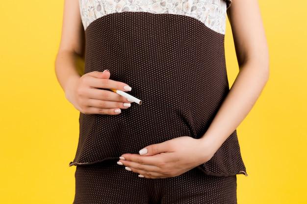 Kobieta w ciąży z papierosem na brzuchu