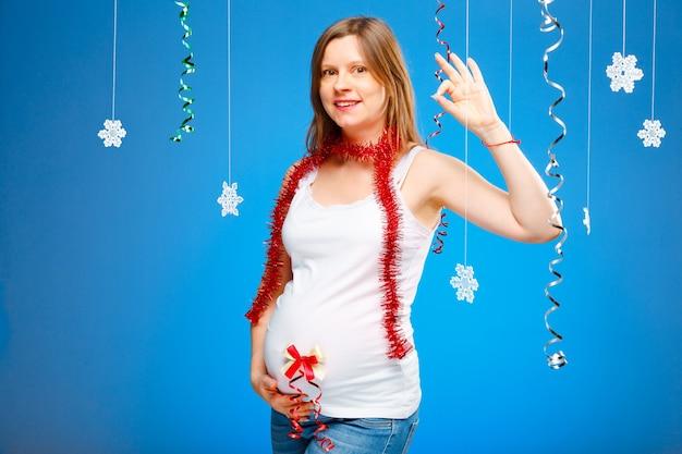Kobieta w ciąży z płatkami śniegu na niebieskim tle i czerwoną girlandą spodziewając się dziecka na boże narodzenie