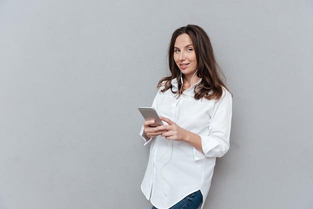 Kobieta w ciąży z telefonem w studio patrząc na kamery na białym tle szarym tle