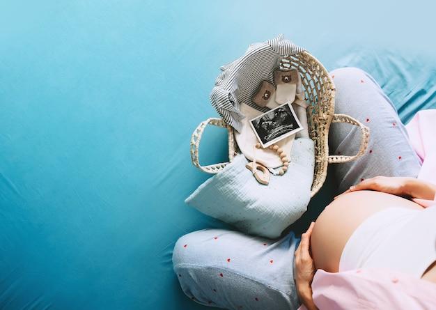Kobieta w ciąży z wiklinowym koszem rzeczy noworodek i obraz usg podczas ciąży
