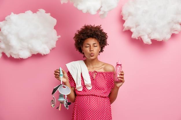 Kobieta w ciąży z zamkniętymi oczami i zaokrąglonymi ustami, czeka na buziaka od męża, pozuje z drobiazgami, ma duży brzuszek, przygotowuje się do macierzyństwa, rodzenia noworodka. rodzicielstwo