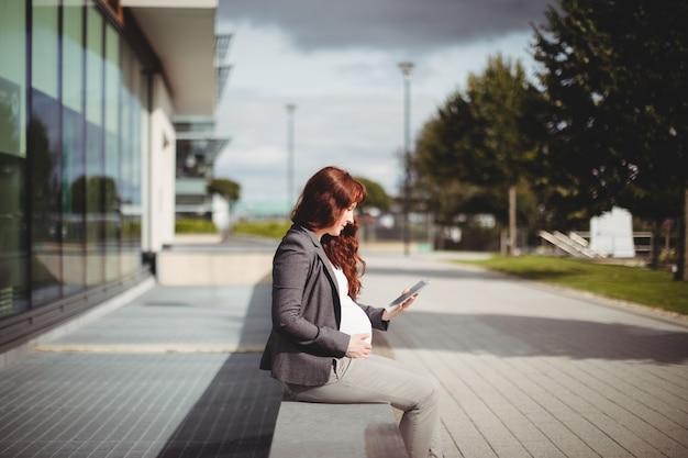 Kobieta w ciąży za pomocą cyfrowego tabletu