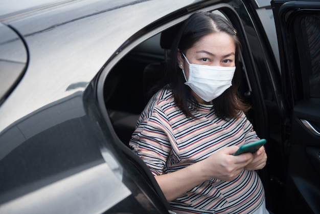 Kobieta w ciąży za pomocą smartfona, siedząc w samochodzie