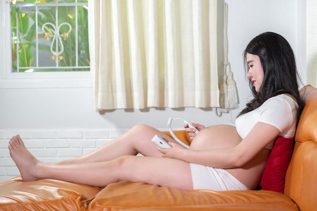 Kobieta w ciąży za pomocą urządzenia droppler płodu do słuchania bicia serca dziecka
