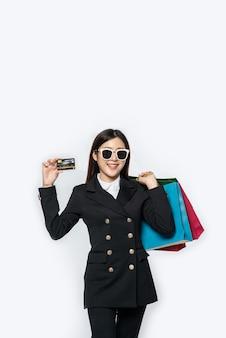 Kobieta w ciemności nosi okulary, idzie na zakupy, nosi karty kredytowe i mnóstwo toreb