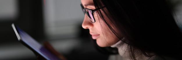 Kobieta w ciemności patrzy na dołączony ekran tabletu.