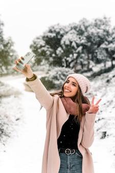 Kobieta w ciepłej odzieży wierzchniej stojącej w lesie i robienia selfie malowniczego śnieżnego krajobrazu podczas korzystania ze smartfona