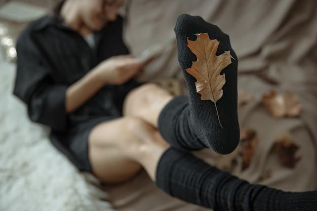 Kobieta w ciepłych pończochach na rozmytym tle i jesienny liść w centrum uwagi.