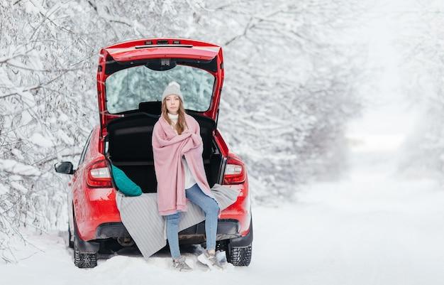 Kobieta w ciepłych ubraniach siedzi w zimowym lesie, opierając się na samochodzie i trzymając filiżankę kawy.