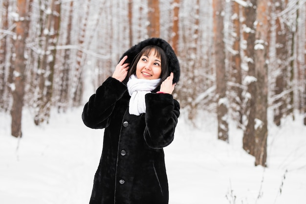 Kobieta w ciepłym płaszczu z futrem w lesie, mroźny zimowy dzień.