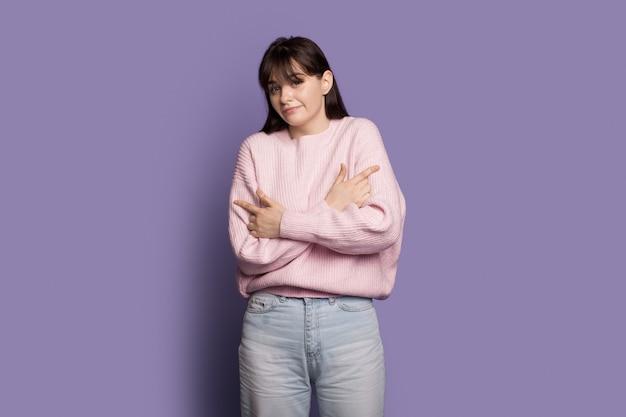 Kobieta w ciepłym swetrze obejmuje się