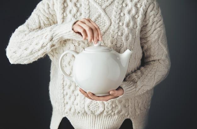 Kobieta w ciepłym swetrze trzyma duży biały imbryk z herbatą w kształcie serca. widok z przodu, drewniany stół grunge. anfas, bez twarzy.