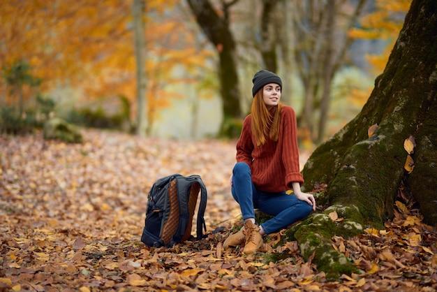 Kobieta w ciepłym ubraniu jesienią siedzi w pobliżu drzewa w lesie
