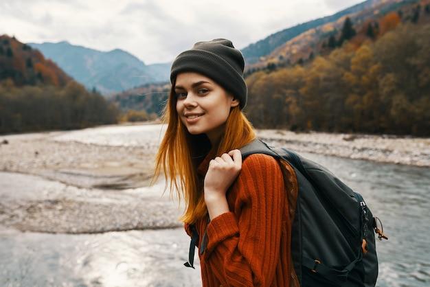 Kobieta w czapce sweter z plecakiem na plecach górskiej rzeki w przyrodzie