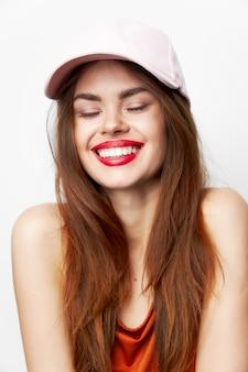 Kobieta w czapce szeroki uśmiech zamknięte oczy nagie ramiona czerwona sukienka na białym tle ściana