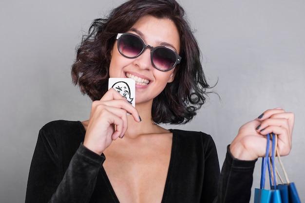 Kobieta w czarnej gryzienie karty kredytowej