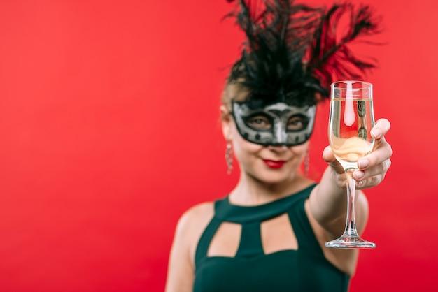 Kobieta w czarnej karnawałowej masce trzyma szampańskiego szkło