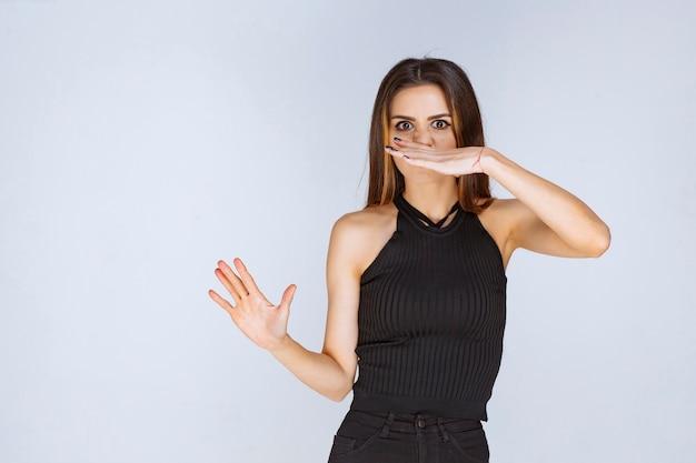 Kobieta w czarnej koszuli czuje nieprzyjemny zapach.