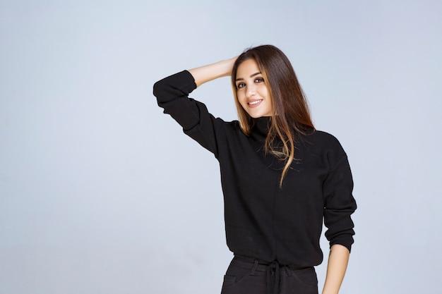 Kobieta w czarnej koszuli dając atrakcyjne i neutralne pozy.