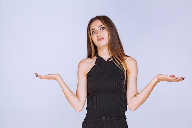 Kobieta w czarnej koszuli dokonywanie prezentacji przy użyciu otwartych rąk.