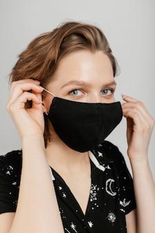 Kobieta w czarnej koszuli i masce