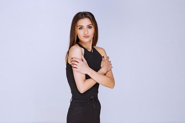 Kobieta w czarnej koszuli krzyżuje ramiona i czuje zimno.