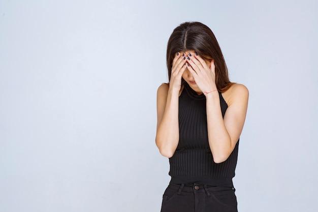 Kobieta w czarnej koszuli ma ból głowy lub płacze.