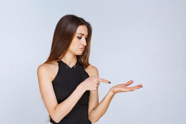 Kobieta w czarnej koszuli, otwierając rękę i trzymając lub prezentując coś.