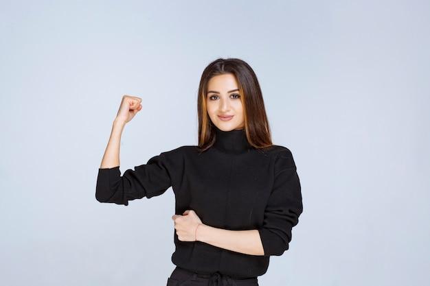 Kobieta w czarnej koszuli pokazując jej pięści jako symbol władzy.