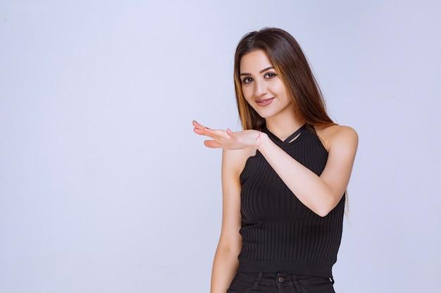 Kobieta w czarnej koszuli pokazująca szacunkowe wymiary przedmiotu.